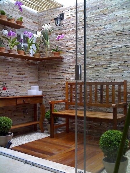 small garden, wooden floor, natural stone wall, wooden floating shelves, wooden table, wooden bench