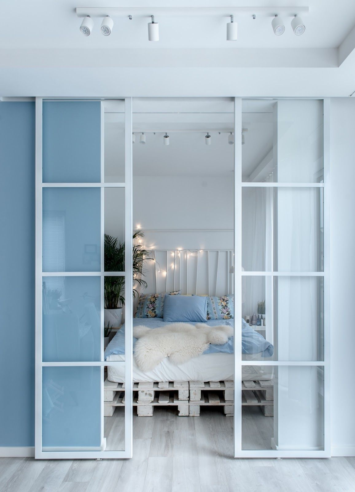 studio apartment, blue partition, glass sliding door, white wooden crate, blue bedding