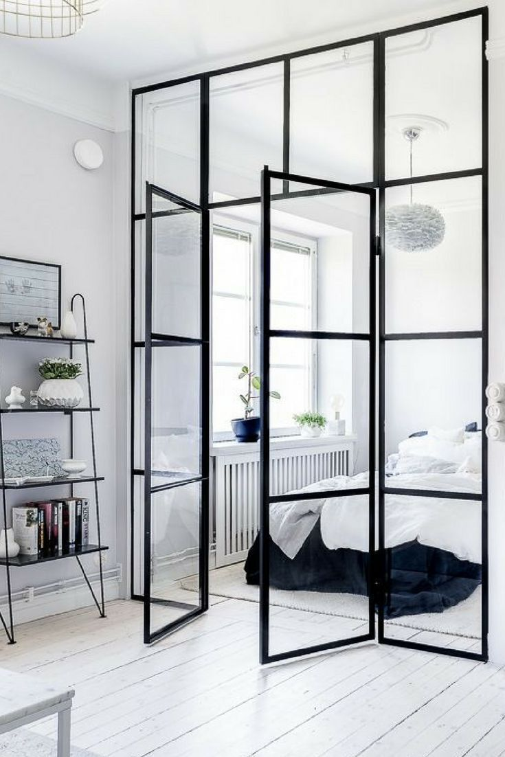 studio apartment, white wooden floor, white wall, bedroom with glass walla nd door, window, white pendant