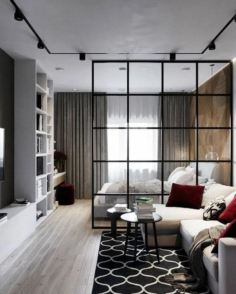 studio apartment, wooden floor, black patterned rug, black round table, white sofa, bedroom with glass partition, white shelves