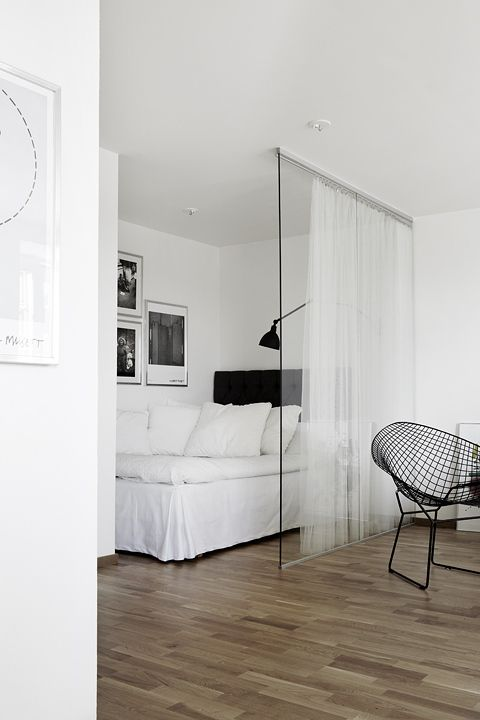 studio apartment, wooden floor, white wall, white bedding, black headboard, black sconce, glass parition, white curtain