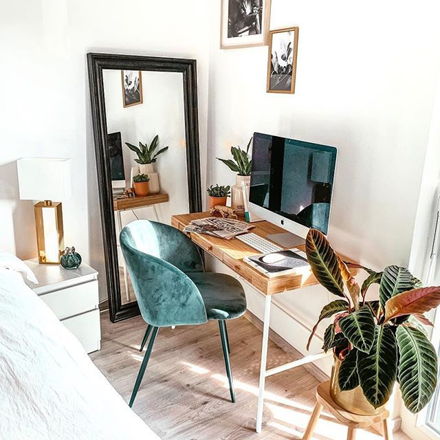 study, wooden table with white legs, green velvety chair, wooden floor, white wall, mirror