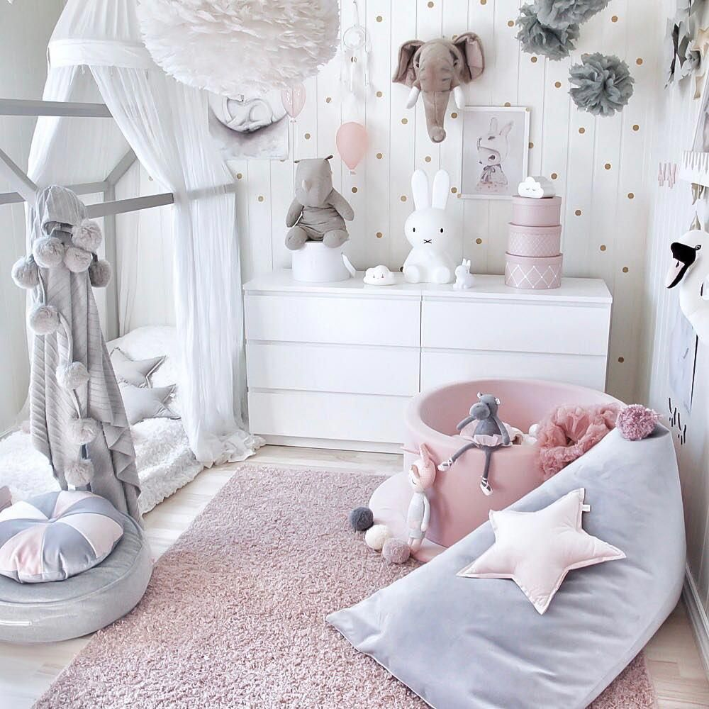 white baby bed, white wooden tent, blue bean bag, pink round box, white cabinet