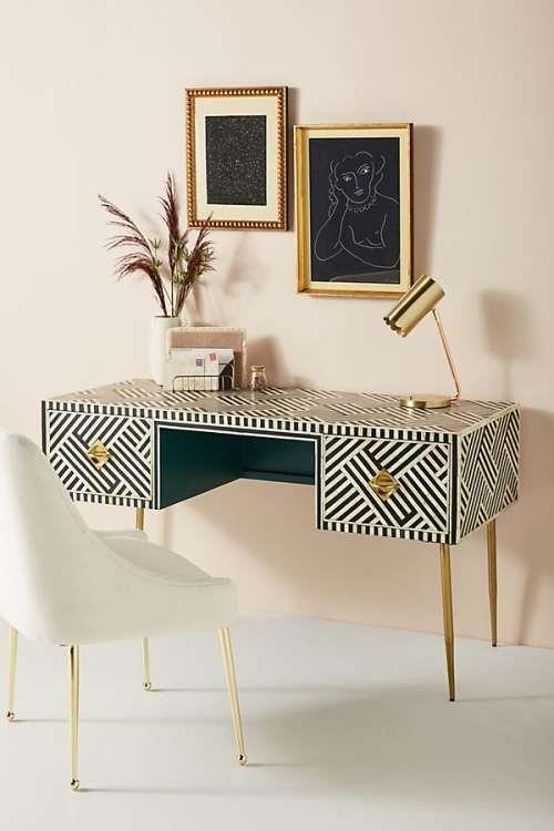 white black patterned table, drawers, golden handler and legs, white chair, golden table lamp
