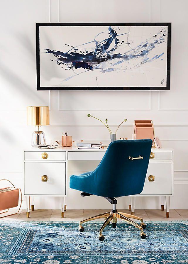 white desk with golden handler, wooden floor, blue chair, blue patterned rug, white wall, golden table lamp