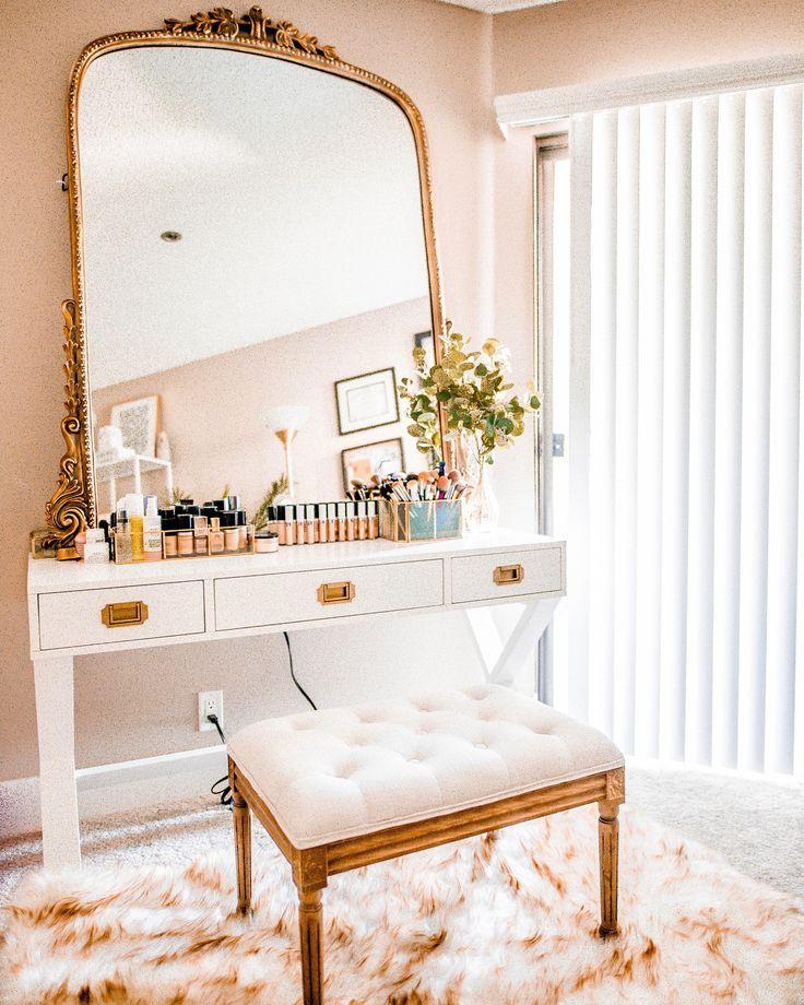 white wooden desk, white floor, white pink rug, golden stool with white cushion, golden framed mirror