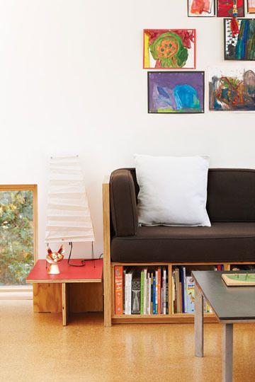 wooden bench, bookshelves, white wall, wooden floor, black cushion