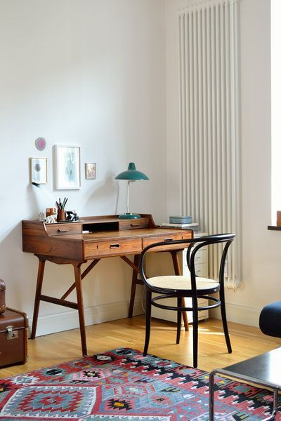wooden study desk, wooden floor, white wall, black chair with white seat
