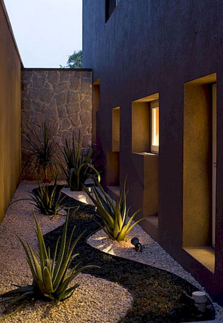 yard, white black stones, stone wall, yellow wall, plants